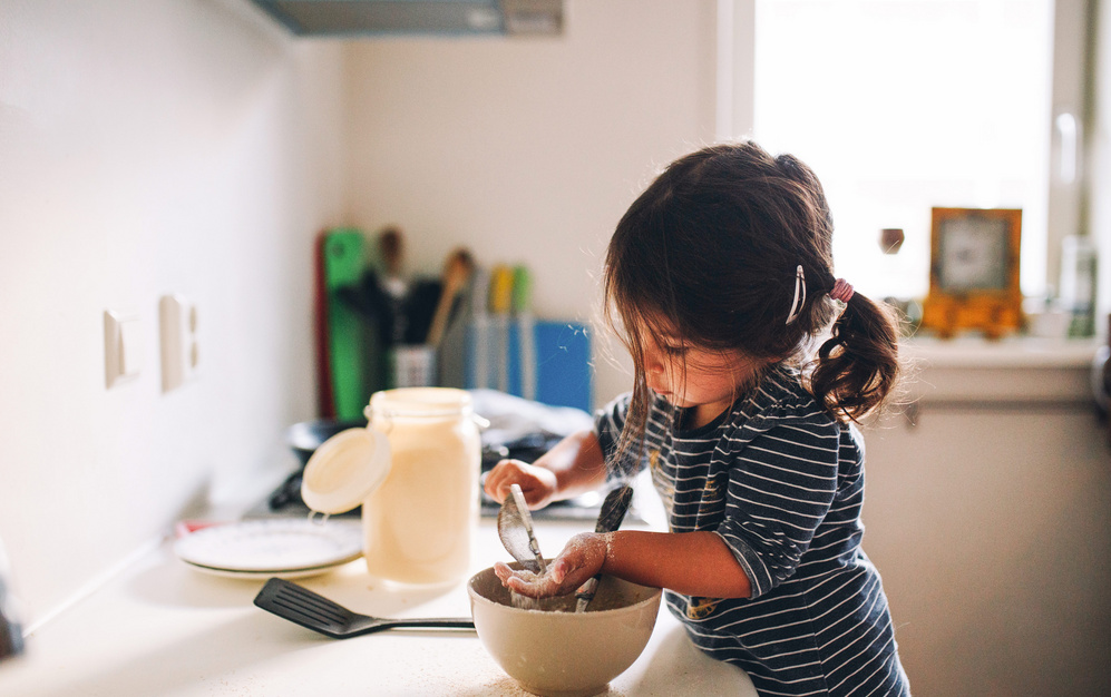 girl kid in the kitchen trying to make something