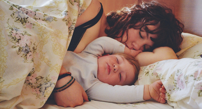 mom and baby sleeping together on bed