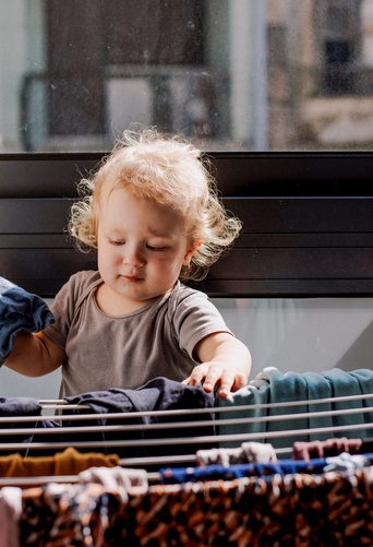 toddler hanging clothes to dry
